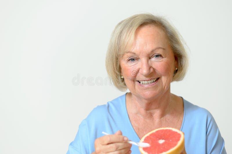 Glückliche gesunde ältere Dame mit einer Orange stockbild