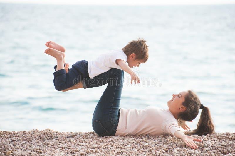Glückliche gesunde Familie, die der lächelnden Mutter und aus nettem kleinem Kind spielen auf Seestrand am Frühsommertag besteht stockbilder
