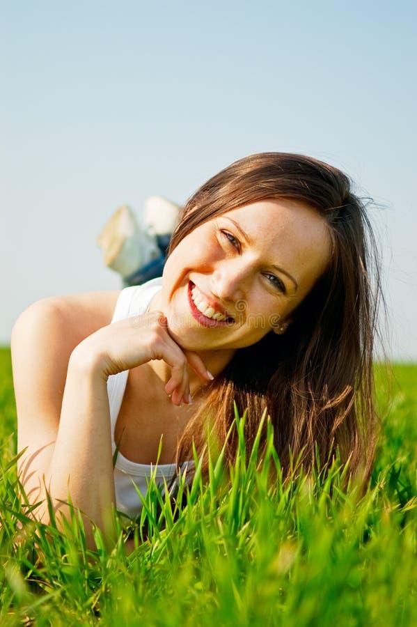 Glückliche gesunde Frau, die im Gras liegt stockbild