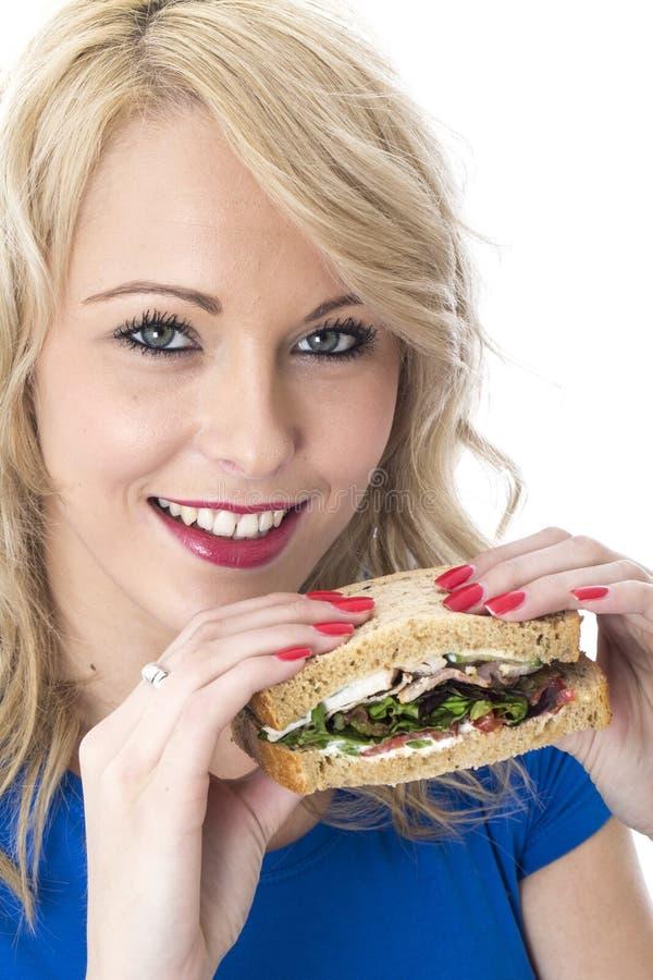 Glückliche gesunde junge Frau, die ein Sandwich isst stockfotografie