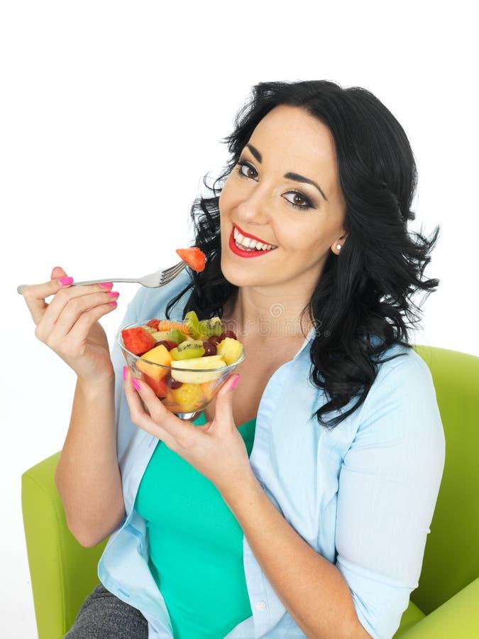 Glückliche gesunde Junge-geeignete Frau, die eine Schüssel frischen exotischen Obstsalat isst lizenzfreies stockfoto