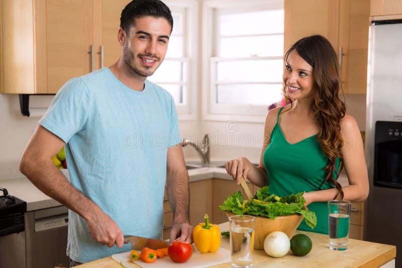 Glückliche gesunde junge Paare des strengen Vegetariers, die zu Hause Gemüse kochen lizenzfreies stockbild