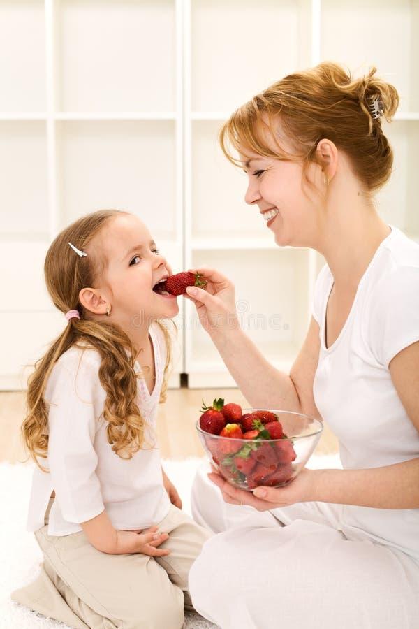 Glückliche gesunde Leute, die frische Erdbeeren essen stockfoto