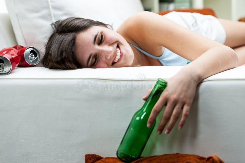 Glückliche getrunkene junge Frau, die auf einem Sofa sich entspannt stockfotografie
