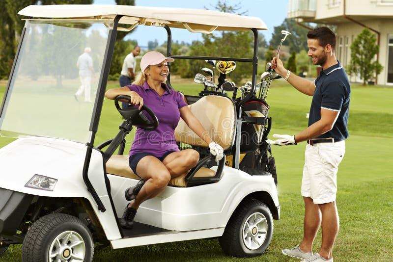 Glückliche Golfspieler, die im Golfmobil sprechen lizenzfreies stockbild