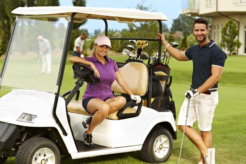 Glückliche Golfspieler und Golfmobil stockfotos