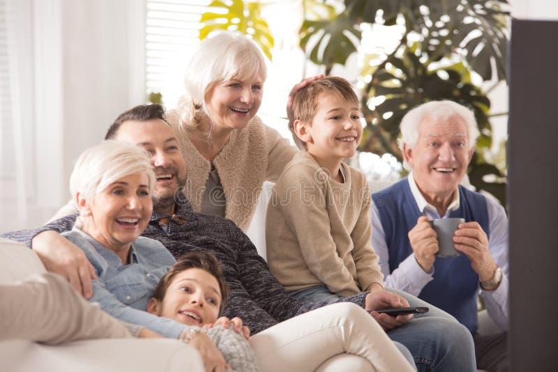 Glückliche große Familie, die fernsieht lizenzfreie stockfotos