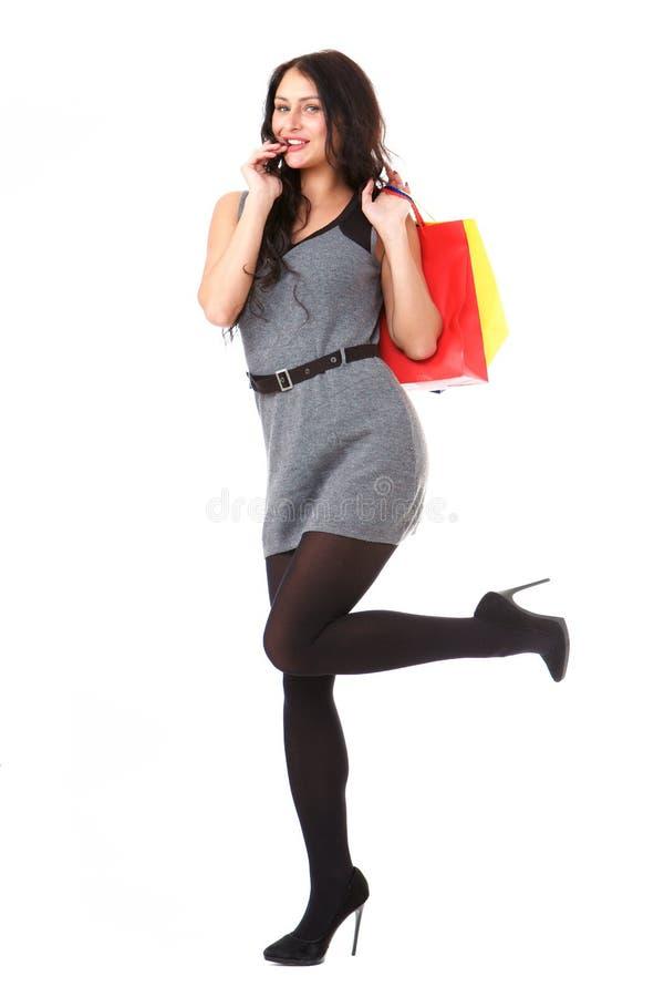 Glückliche große Frau in voller Länge mit bunten Einkaufstaschen lizenzfreie stockbilder