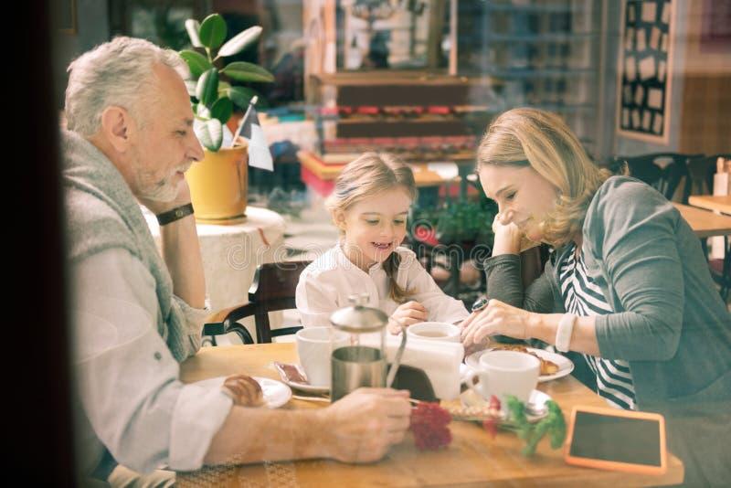 Glückliche Großeltern, die ihre Familienzeit mit nettem intelligentem Mädchen genießen stockfoto