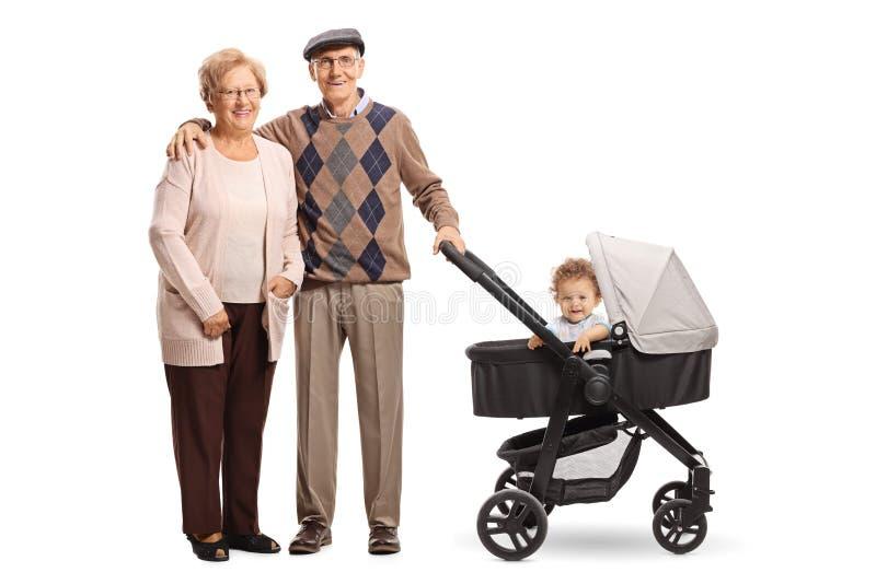 Glückliche Großeltern, die mit einem Kinderwagen und ihrem Enkel stehen stockfotos