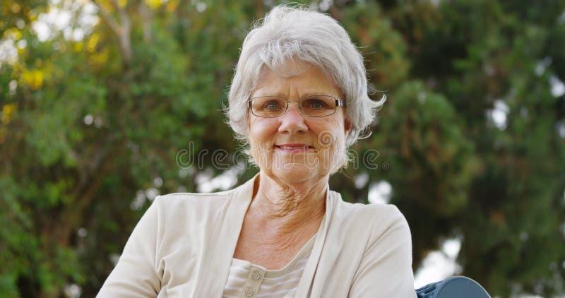 Glückliche Großmutter, die auf Bank sitzt lizenzfreies stockfoto
