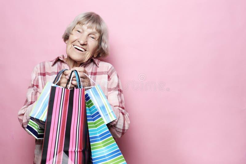 Glückliche Großmutter mit Einkaufstaschen über rosa Hintergrund Lebensstil und Leutekonzept Ältere Frau - glückliche Zeit stockbild