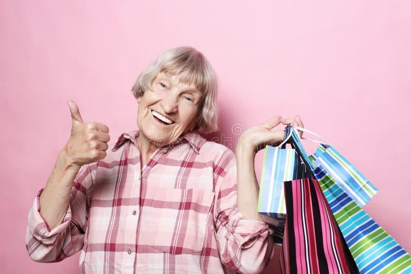 Glückliche Großmutter mit Einkaufstaschen über rosa Hintergrund Lebensstil und Leutekonzept stockfotos