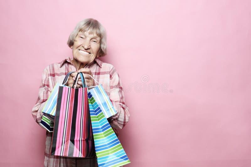 Glückliche Großmutter mit Einkaufstaschen über rosa Hintergrund Lebensstil und Leutekonzept stockfoto