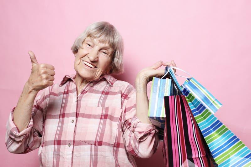 Glückliche Großmutter mit Einkaufstaschen über rosa Hintergrund Lebensstil und Leutekonzept lizenzfreie stockfotografie