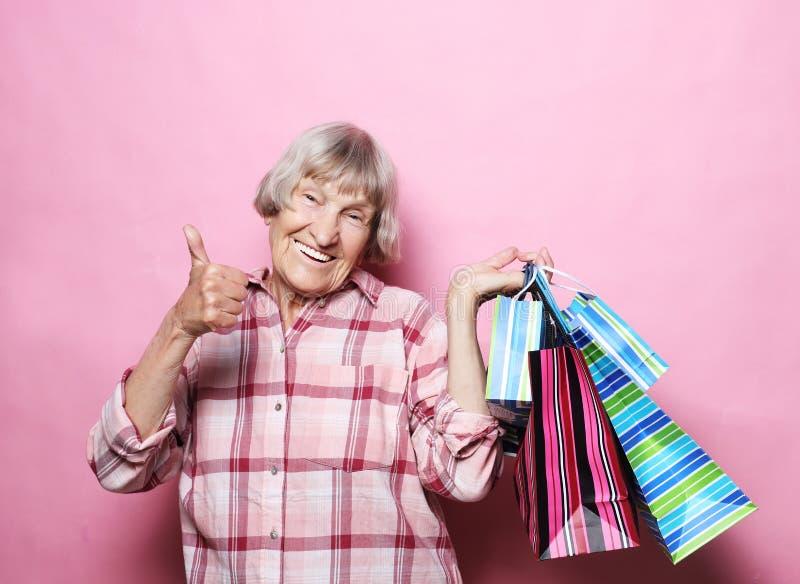 Glückliche Großmutter mit Einkaufstaschen über rosa Hintergrund Lebensstil und Leutekonzept stockbild