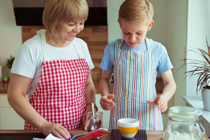 Glückliche Großmutter mit ihrem Enkelkind, das Spaß während des Backens von m hat stockfoto