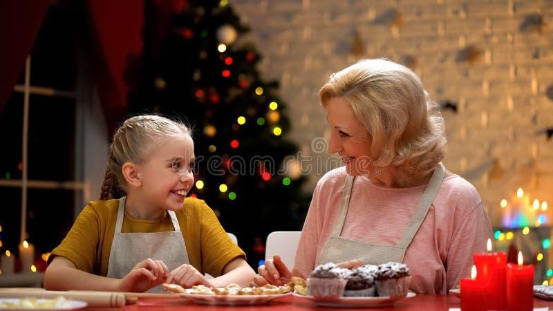 Glückliche Großmutter und Mädchen, die, gefallen mit Weihnachtsbäckerei, Feiertage lächelt stockbilder