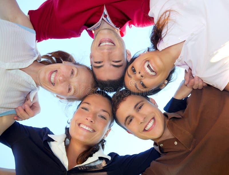 Glückliche Gruppe der Freunde in den Kreisköpfen von unterhalb stockbilder