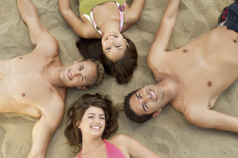 Glückliche Gruppe Freunde, die auf Sand liegen stockfotografie