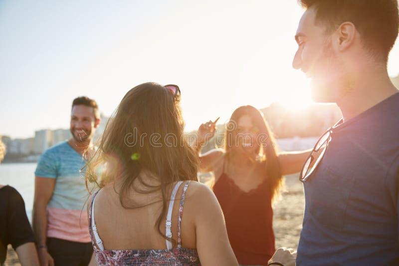 Glückliche Gruppe Freunde, die auf Strand tanzen stockbild