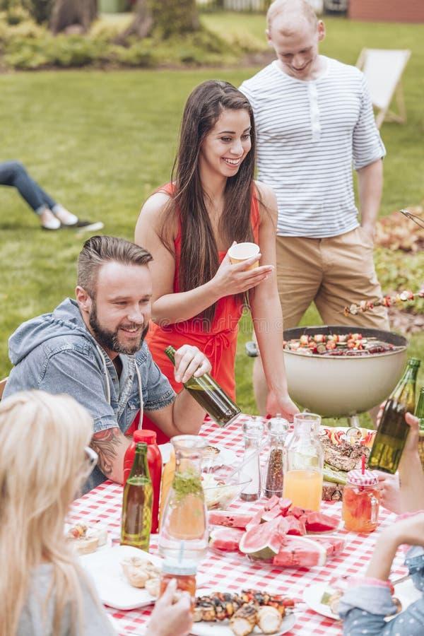 Glückliche Gruppe Freunde, die eine Grillpartei durch eine Tabelle voll von f haben stockbild