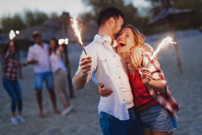 Glückliche Gruppe Freunde, die Wunderkerzen beleuchten und Freiheit genießen lizenzfreies stockfoto
