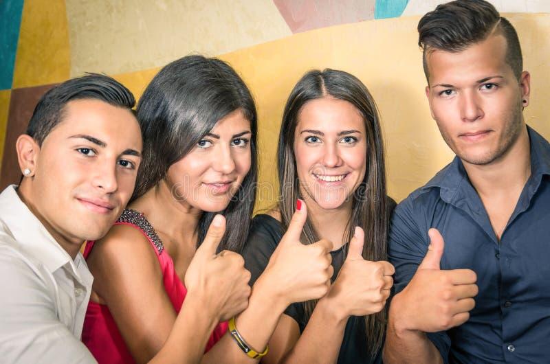 Glückliche Gruppe Freunde mit den Daumen oben stockbild