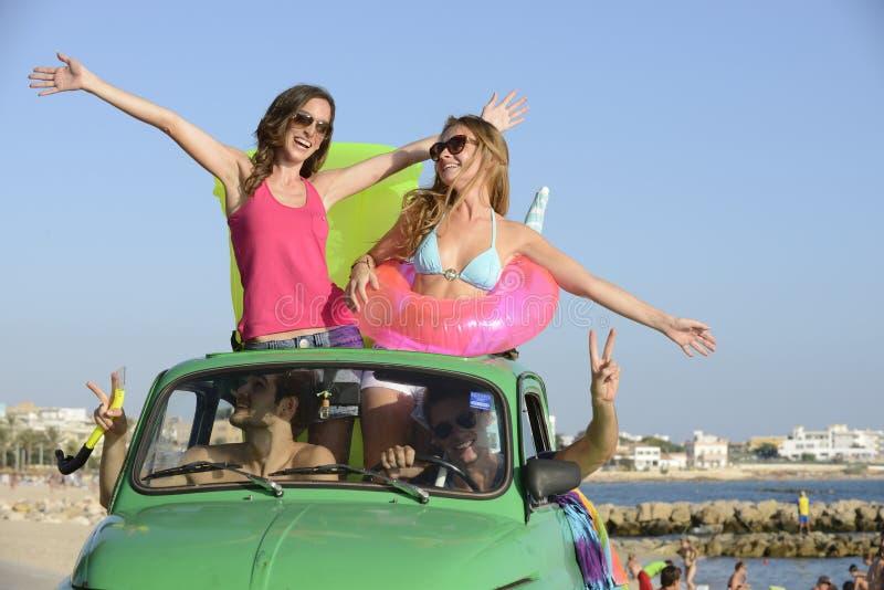 Glückliche Gruppe Freunde mit kleinem Auto auf Strand lizenzfreie stockbilder