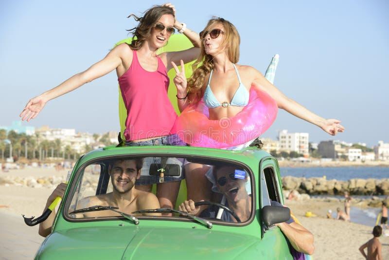 Glückliche Gruppe Freunde mit kleinem Auto auf Strand stockfotos