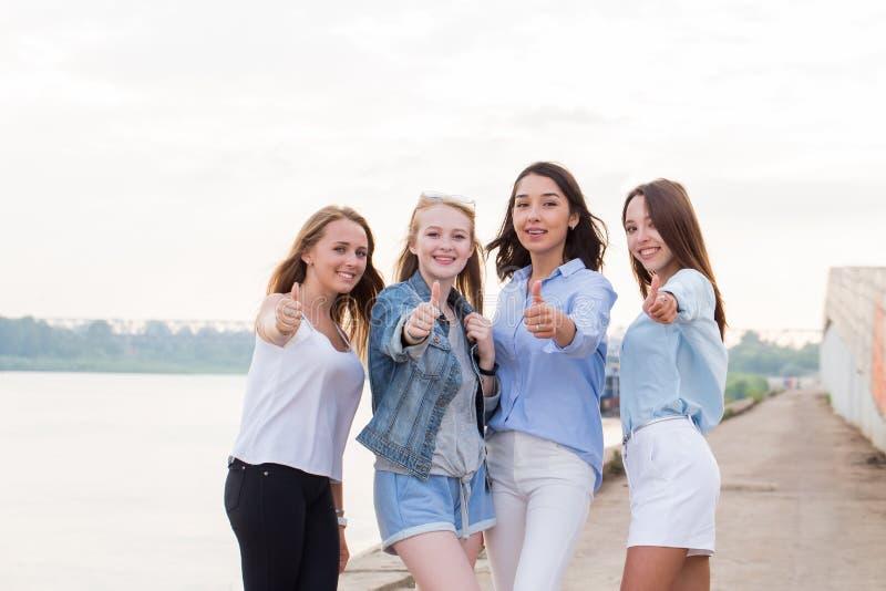 Glückliche Gruppe Freundinnen mit den Daumen herauf schauende Kamera im Freien und Lächeln stockbilder