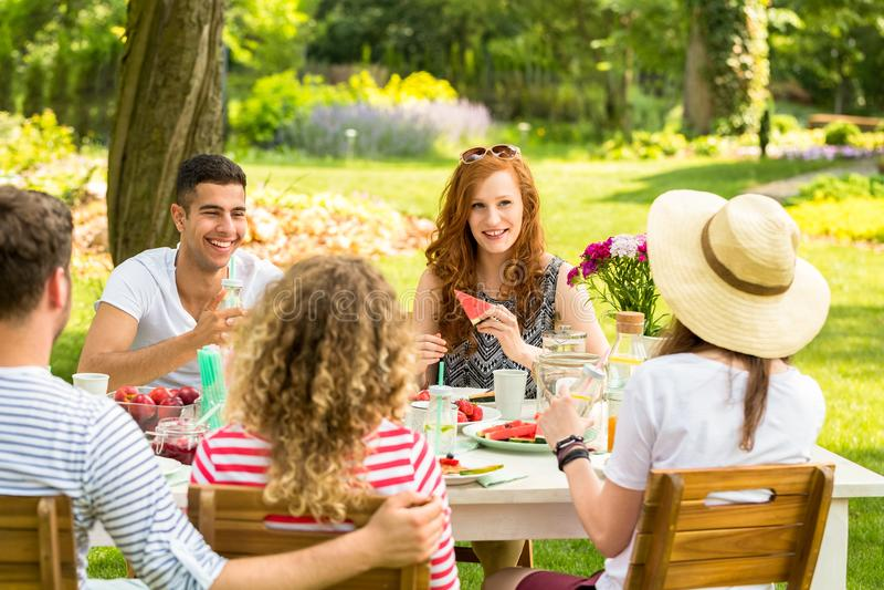Glückliche Gruppe Jugendlichen, die Wassermelone essen und Spaß während haben lizenzfreies stockfoto