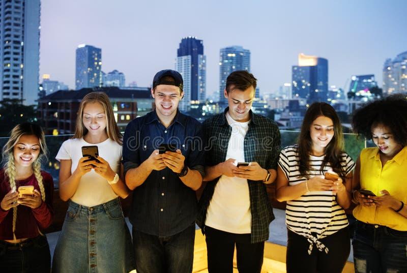 Glückliche Gruppe junge Erwachsene unter Verwendung der Smartphones im Stadtbild stockbilder
