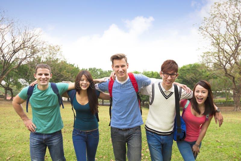 Glückliche Gruppe Studenten, die zusammen gehen stockbilder