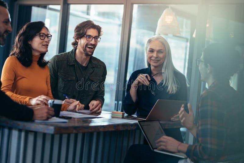 Glückliche Gruppe von Personen, die Sitzung im Büro hat stockfotos