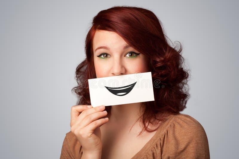 Glückliche hübsche Frau, die Karte mit lustigem smiley hält stockbild