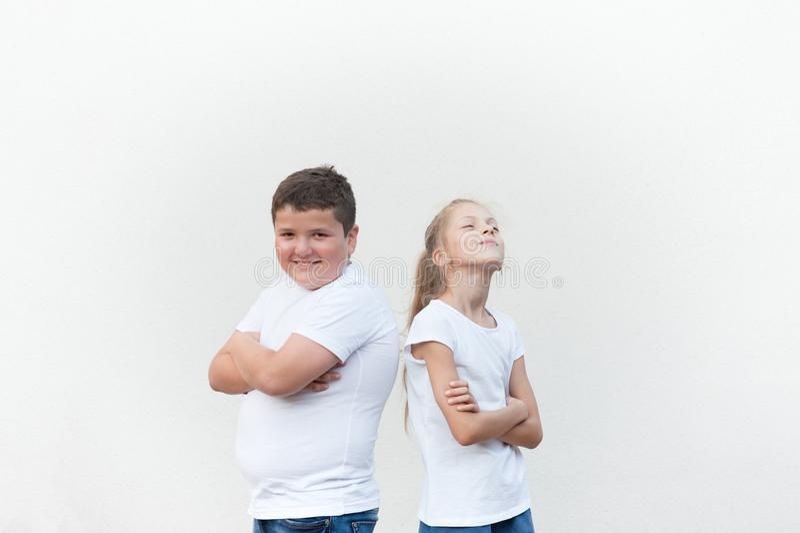 Glückliche hübsche Kinderfetter Junge und dünnes Mädchen zurück zu Rückseite auf hellem Hintergrund stockfotografie