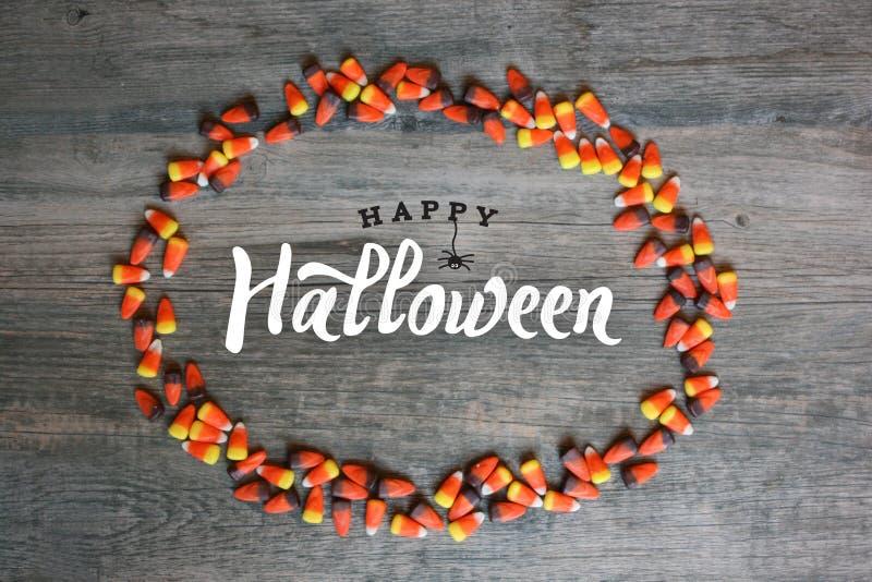 Glückliche Halloween-Kalligraphie mit Süßigkeits-Mais-ovaler Grenze über dem rustikalen hölzernen Hintergrund, horizontal lizenzfreie stockfotografie