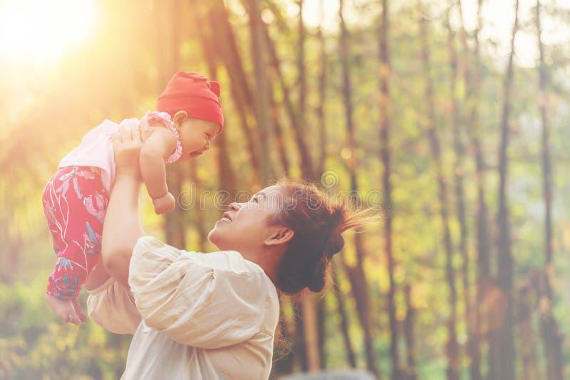 Glückliche harmonische Familie; Mutter- und Babyfreien Ihre schöne Mutter wirft Baby oben und lacht und spielt im Parksommer lizenzfreies stockbild
