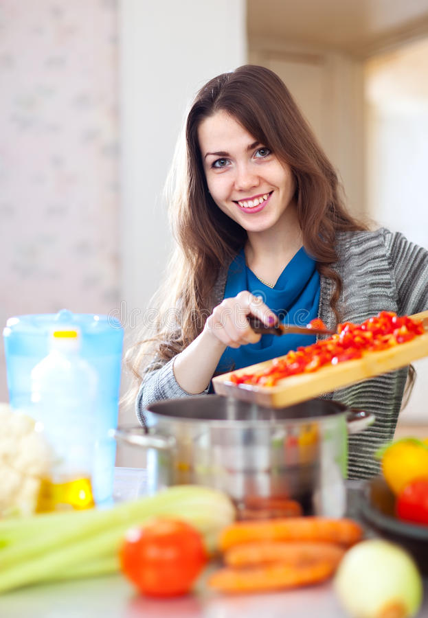 Glückliche Hausfrau, die das Veggiemittagessen kocht stockfotos