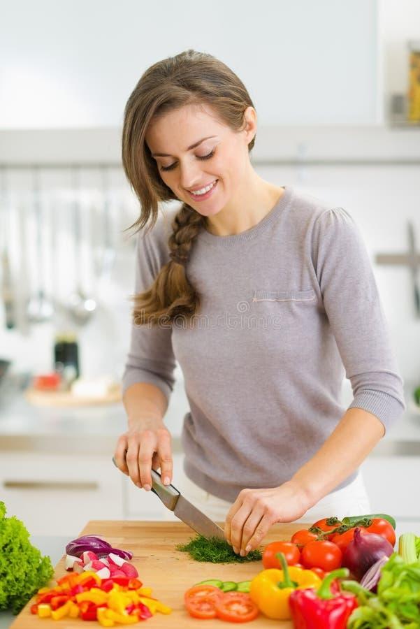 Glückliche Hausfrau, die frischen Dill in der Küche schneidet lizenzfreie stockfotos
