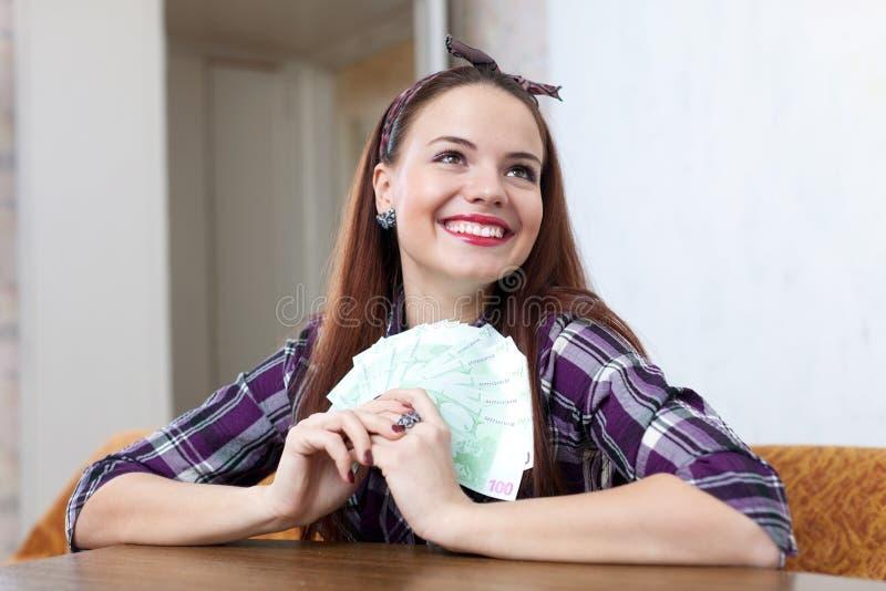 Glückliche Hausfrau mit vielen Euro stockfotografie
