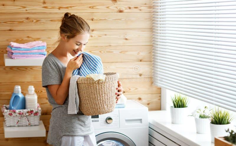 Glückliche Hausfraufrau in der Waschküche mit Waschmaschine stockbilder