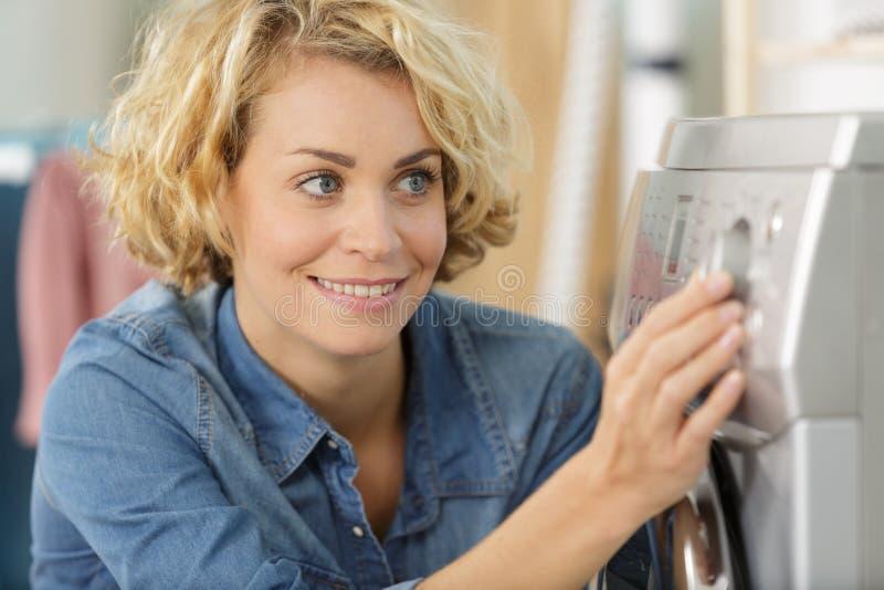 Glückliche Hausfraufrau in der Waschküche lizenzfreies stockbild