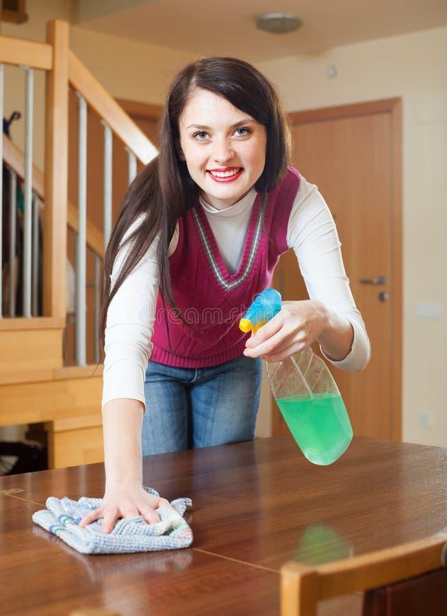Glückliche Hausfraureinigungstabelle mit Möbelpolitur lizenzfreie stockfotos
