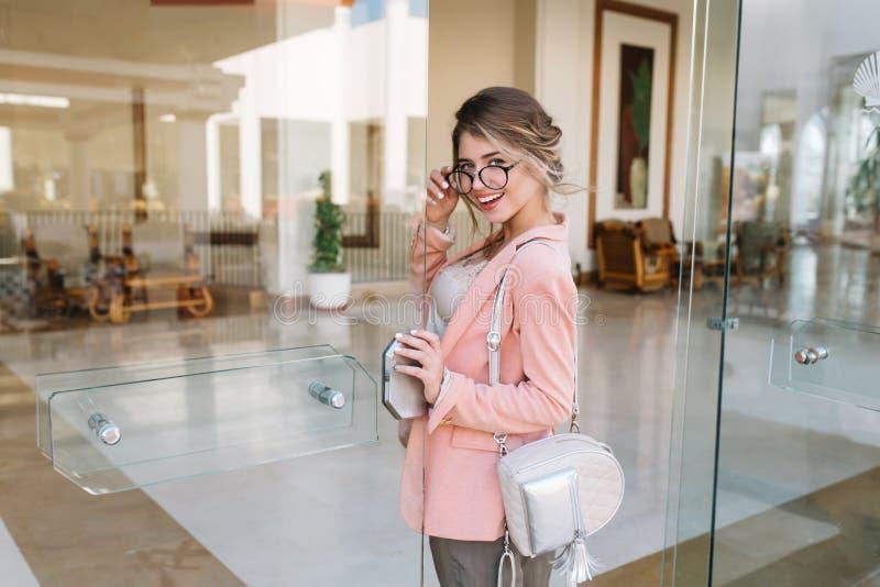 Glückliche hereinkommende Glastür der jungen Frau in modernes Hotel, Café, Geschäftszentrum Tragende stilvolle Gläser, rosa Jacke lizenzfreie stockfotos