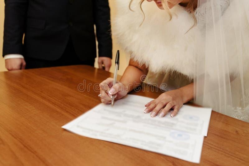 Glückliche herrliche Braut und stilvoller Bräutigam, die amtliche Urkunde unterzeichnet stockbilder