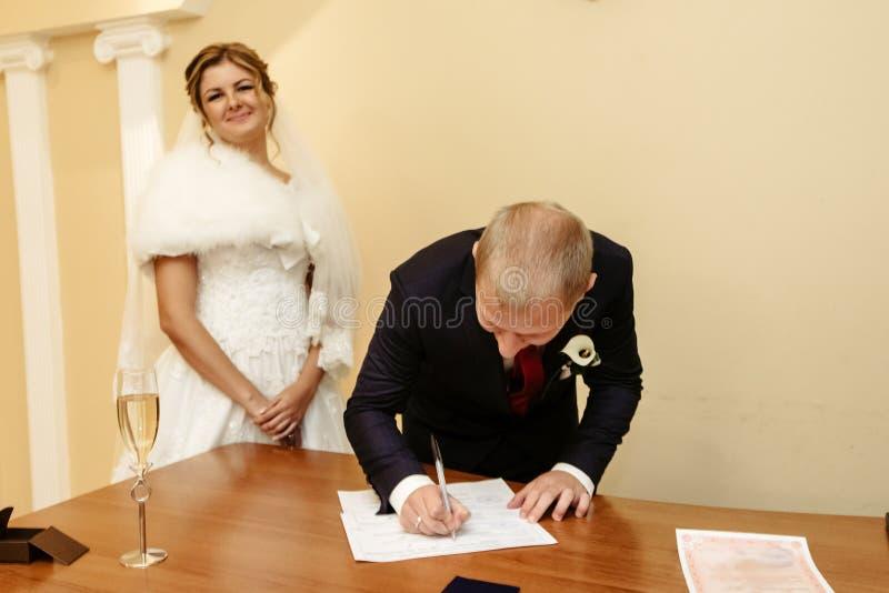 Glückliche herrliche Braut und stilvoller Bräutigam, die amtliche Urkunde unterzeichnet lizenzfreie stockbilder