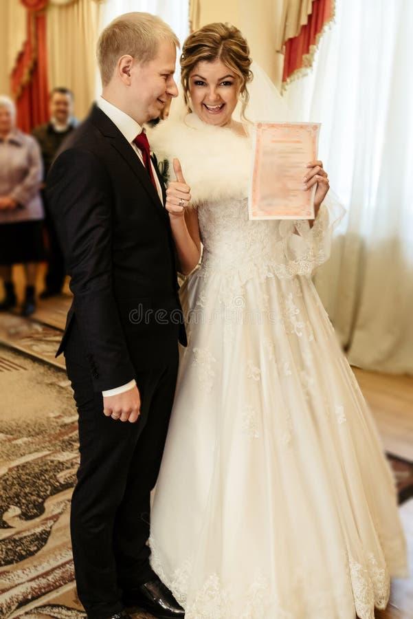 Glückliche herrliche Braut und stilvoller Bräutigam, die amtliche Urkunde verwahrt stockfoto