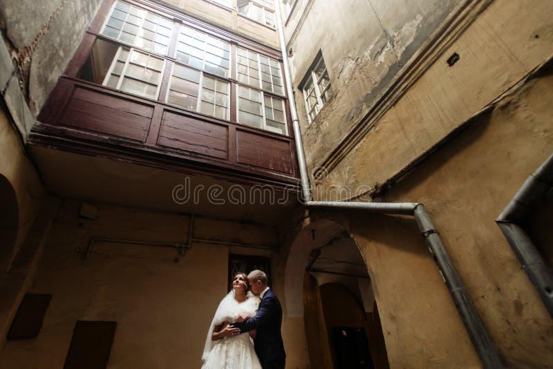 Glückliche herrliche Braut und stilvoller hübscher Bräutigam, die auf backg umarmt lizenzfreies stockfoto